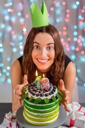 Eighteen girl with happy birthday cake on festive light background photo