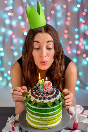 blow out: Eighteen girl with happy birthday cake blowing up candles on festive light background Stock Photo