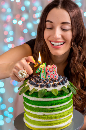 Eighteen girl with happy birthday cake lighting candles on festive light background photo