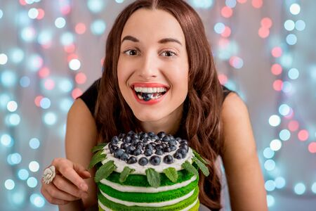 festal: Beautiful girl with happy birthday cake tasting the grape on festive light background Stock Photo
