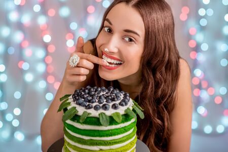 Beautiful girl tasting happy birthday cake by licking her finger with cream on festive light background photo