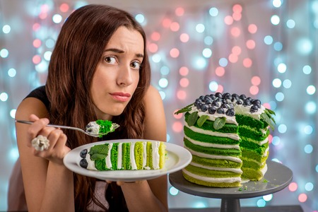 Sad girl thinking eat or not to eat happy birthday cake sitting on festive light background photo