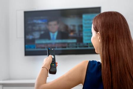 リモート自宅のソファに座っているとテレビでニュースを見ている若い女性。背面図