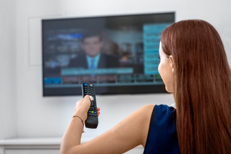 news room: Young woman watching news on television with remote sitting on the sofa at home. Back view Stock Photo
