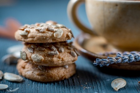 Sweet cookies with sunflower seeds and a cup of red tea with lavender on blue wooden table