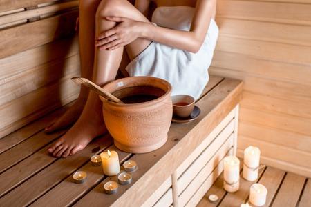 finnish bath: Young woman in white towel resting in Finnish sauna