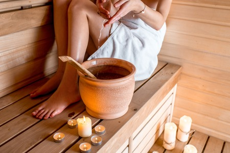 young girl bath: Young woman in white towel pouring water while resting in Finnish sauna Stock Photo