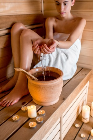 ewer: Young woman in white towel pouring water while resting in Finnish sauna Stock Photo