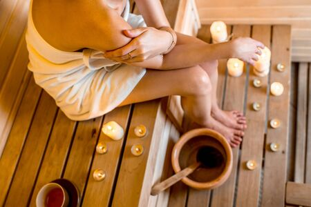 finnish bath: Young woman taking care of her legs sitting in Finnish sauna with lighted candles