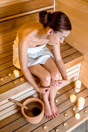 ewer: Young woman taking care of her legs sitting in Finnish sauna with lighted candles