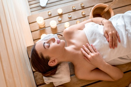 finnish bath: Young woman in white towel lying in Finnish sauna, top view Stock Photo