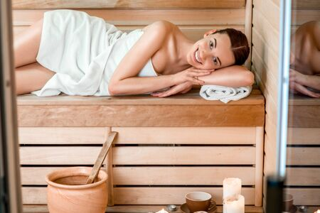 finnish: Young woman in white towel lying in Finnish sauna. Stock Photo
