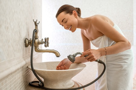 woman washing face: Young woman washing face in the classic style bathroom