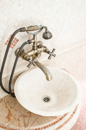 Classic round sink in the bathroom with mosaic photo