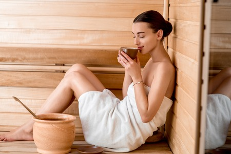 woman bath: Young woman in white towel drinking tea sitting in Finnish sauna