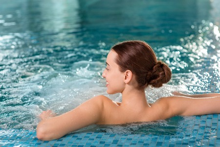 hair spa: Young woman enjoying jacuzzi in the swimming pool at the hotel spa