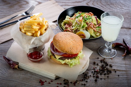 American lunch with hamburger, fries, salad and lemonade on wooden table