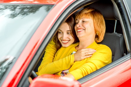 Happy mother with her daughter hugging and driving red car photo
