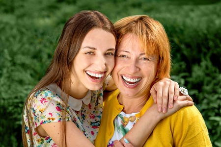 two person only: Mother with her daughter smiling and hugging dressed in yellow in the park