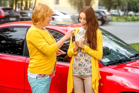 Mother giving car keys as a gift to her daughter near red car on the parking photo