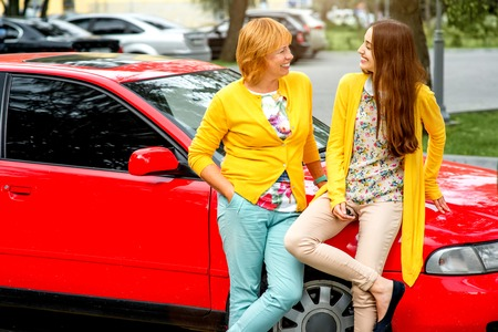 Mother talking with her daughter near red car on the parking photo