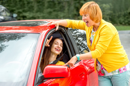 Mother teaching her daughter to drive the car photo