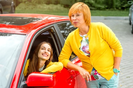 Mother with her daughter near red car in the parking photo