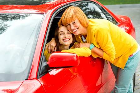 Mother hugging her daughter in the car on the parking photo