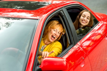 Happy mother with her daughter driving red car photo