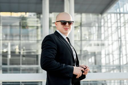 businesswear: Businessman or banker standing outside the airport or contemporary building