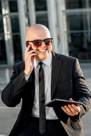 businesswear: Businessman or banker speaking phone outside the airport or contemporary building