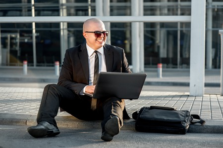 businesswear: Businessman or banker working with laptop outside the airport or contemporary building