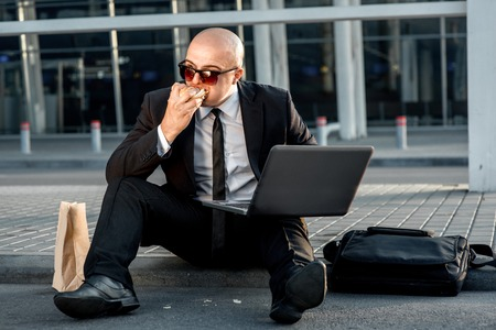 businesswear: Businessman or banker working with laptop and having snack with burger outside the airport or contemporary building