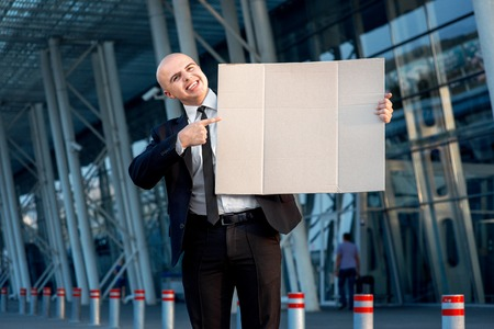 businesswear: Businessman with big cardboard outside the airport or contemporary building