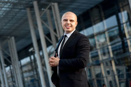 businesswear: Businessman or banker working outside the airport or contemporary building