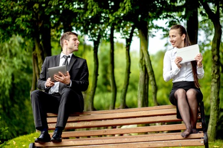 keek: Young Business couple sitting on the bench and reading or working with tablets outdoors.
