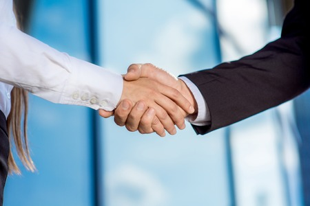 business  deal: business couple shaking hands outdoors on contempopary background