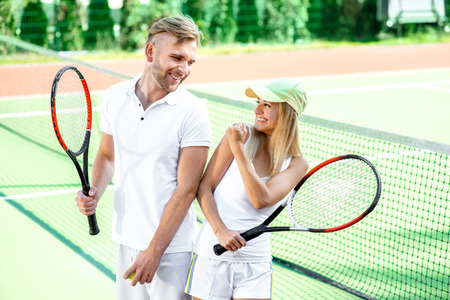 Young married couple playing tennis in white sportwear on the tennis court outside in the summer Stock Photo