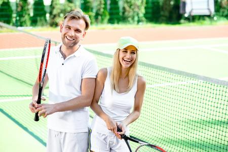 jugando tenis: Pareja casada joven que juega al tenis en prendas blancas en la cancha de tenis al aire libre en el verano