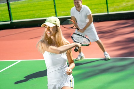 male tennis players: Young married couple playing tennis in white sportwear on the tennis court outside in the summer Stock Photo