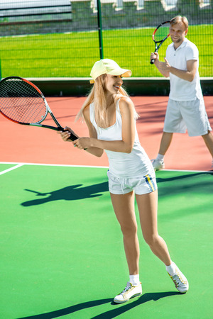 Young married couple playing tennis in white sportwear on the tennis court outside in the summer photo