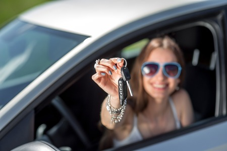 new driver: Car driver woman happy showing car keys out window