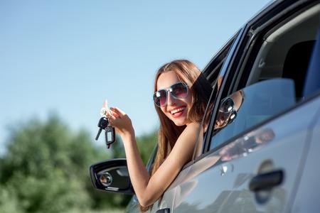 chicas comprando: Mujer piloto de coche teclas que muestra feliz del coche por la ventana Foto de archivo