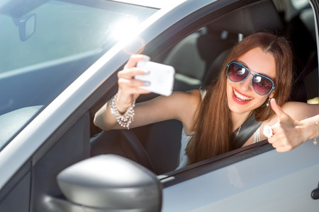are taking: Smiling young woman taking selfie picture with smart phone camera outdoors in car
