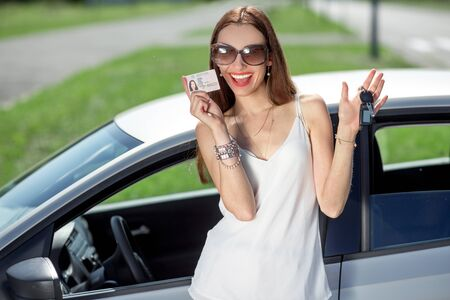 successfully: Young woman showing a key and license in front of the car. Girl pass successfully driving exam.