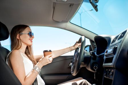 new driver: Happy young woman with coffee to go driving her car Stock Photo