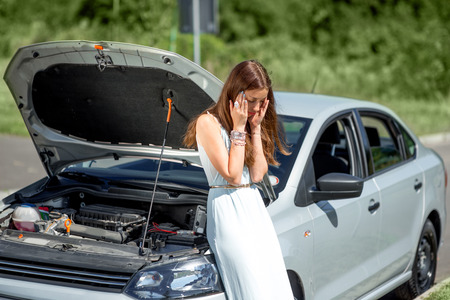breakage: A woman waits for assistance near her car broken down on the road side.