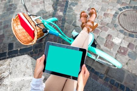 Tenir tablette dans les mains à vélo sur fond dans la ville Banque d'images