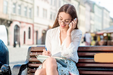 Young woman sitting on the bench with tablet and speaking phone photo