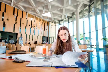 comedor escolar: Muchacha que estudia en la cantina de la Universidad con dulce y torta Foto de archivo